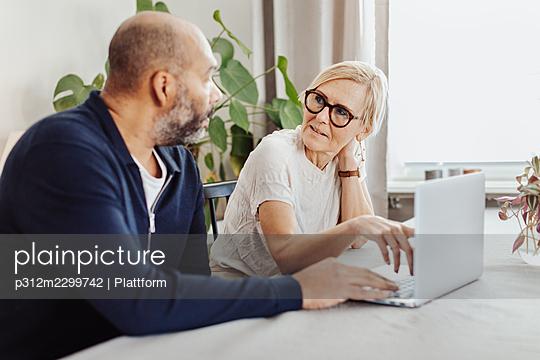 Couple using laptop at home - p312m2299742 by Plattform
