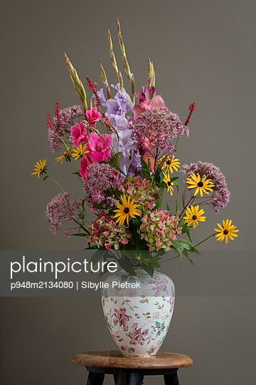 Bunter Sommerblumenstrauß in einer Vase mit Verzierung auf Holzschemel vor brauner Wand. - p948m2134080 von Sibylle Pietrek