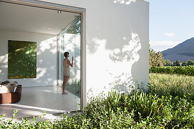 Woman standing at window in modern house - p1023m1146385 by Astronaut Images