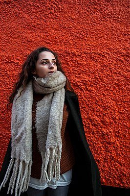 Young woman wearing scarf and coat on autumnal day standing in front of orange wall - p1047m2150242 by Sally Mundy