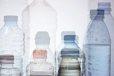 Used water bottles and white background - p1166m2106088 by Cavan Images