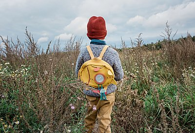 back of a young school boy looking at a field of wild flowers thinking - p1166m2136887 by Cavan Images