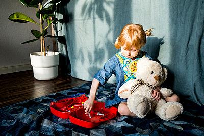 Playful blond girl aspiring doctor while holding teddy bear at home - p300m2275436 by Irina Heß