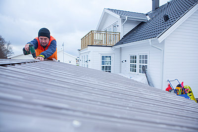 Man repairing roof - p312m1164650 by Malcolm Hanes