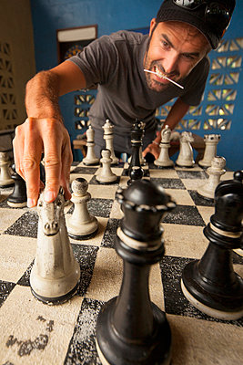Mid adult man moving chess piece on giant chess board - p429m1022634 by Romona Robbins Photography