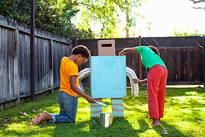 Two brothers painting home made robot light blue in garden - p429m974539 by Kevin Kozicki