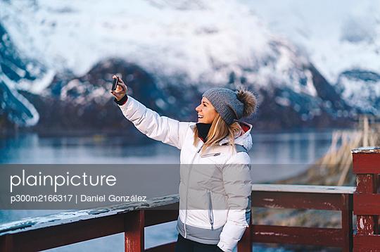 Happy tourist taking a selfie at Hamnoy, Lofoten, Norway - p300m2166317 by Daniel González