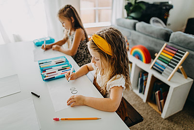 Two young girls drawing with colorful markers at table - p1166m2212384 by Cavan Images