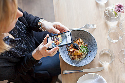 High angle view of woman photographing food through mobile phone in restaurant - p1185m1027514f by Astrakan
