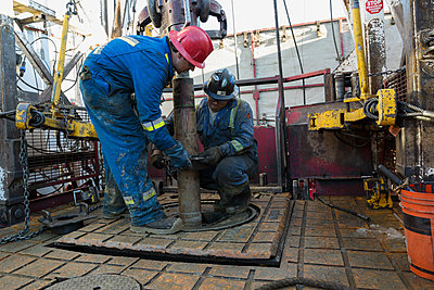 Male workers working drilling rig equipment gas plant - p1192m1128003f by Hero Images