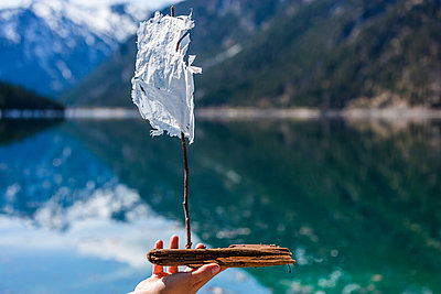 Austria, Tyrol, Lake Plansee, woman holding model sailboat - p300m1023370f by Tom Chance