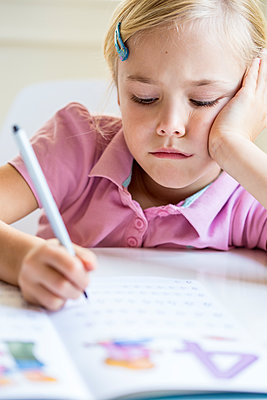 Portrait of bored little girl writing numbers in exercise book - p300m2012623 by Jana Fernow