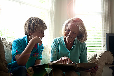 Smiling woman showing photo album to grandson while sitting on sofa at home - p300m2287140 by LOUIS CHRISTIAN