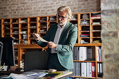 Male design professional examining fabric in office - p300m2300422 by Rainer Berg