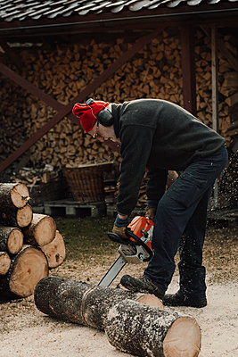 Senior man using chainsaw - p312m2190971 by Jennifer Nilsson