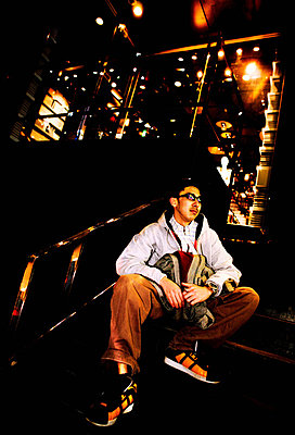 Portrait of young man sitting on steps in nightclub - p924m805964f by Shuntaro Hosokawa