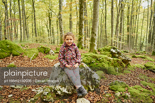 Joyful small kid in warm clothes looking at camera and smiling while s - p1166m2192036 by Cavan Images