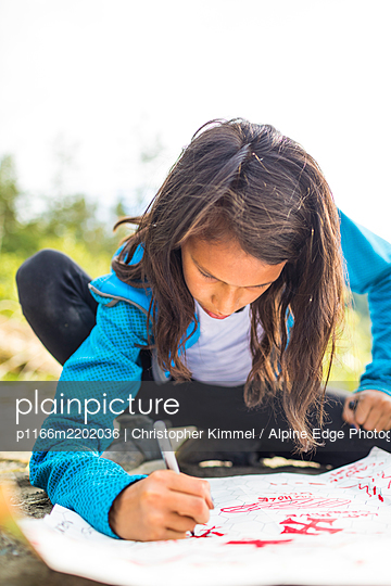 Girl drawing treasure map - p1166m2202036 by Christopher Kimmel / Alpine Edge Photography
