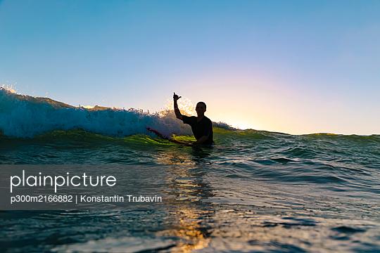 Surfer making surfer sign sitting on surfboard, Bali, Indonesia - p300m2166882 by Konstantin Trubavin