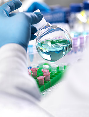 Cropped hand of scientist holding chemical in container for medical testing - p1166m2001380 by Cavan Images