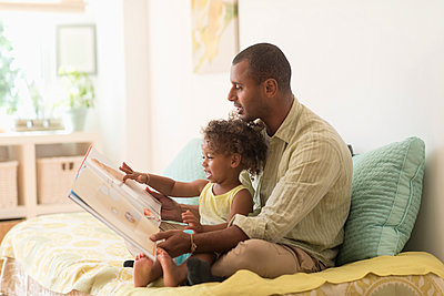 Father and daughter reading book on bed - p555m1420665 by JGI/Tom Grill