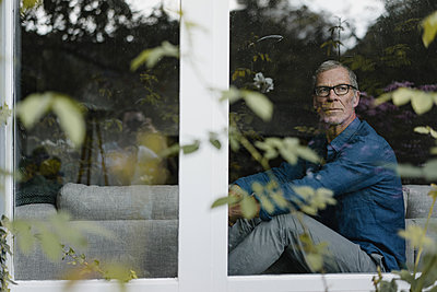Mature man looking out of window - p586m2134723 by Kniel Synnatzschke