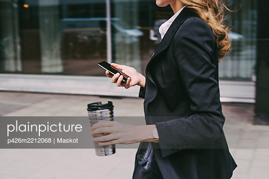 Midsection of businesswoman with coffee mug and phone in city - p426m2212068 by Maskot