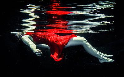 Frau im roten Kleid treibt Unterwasser - p1019m1461902 von Stephen Carroll