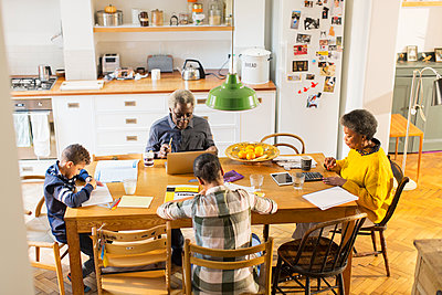 Grandparents at dining table with grandchildren doing homework - p1023m1583925 by Tom Merton
