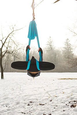 Young woman practicing aerial yoga outdoors - p1026m1025128f by Patrick Frost