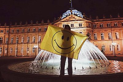 Deutschland, Stuttgart, Frau mit Smiley Flagge auf Brunnen - p1301m2196932 von Delia Baum