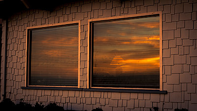 Sunset is reflected in the window - p1324m1165165 by Michael Hopf