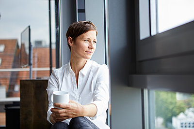 Businesswoman sitting in office with cup of coffee looking out of window - p300m2012971 by Rainer Berg