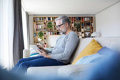Mature man sitting on couch at his living room using tablet - p300m2030308 von Rainer Berg