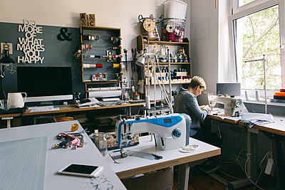 Woman using sewing machine in studio - p300m2070031 by Visualspectrum