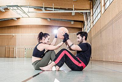 Man and woman practising with medicine ball in sports hall - p300m2144782 von Stefanie Baum
