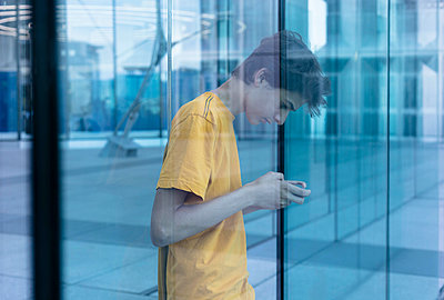 Teenager using smartphone at La Defense - p445m1452425 by Marie Docher