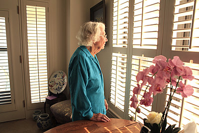 Older Caucasian woman looking out window - p555m1408818 by Shestock
