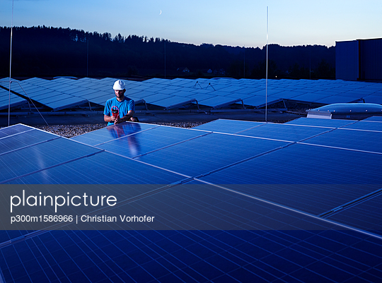 Worker with measuring device checking solar plant in the evening - p300m1586966 von Christian Vorhofer