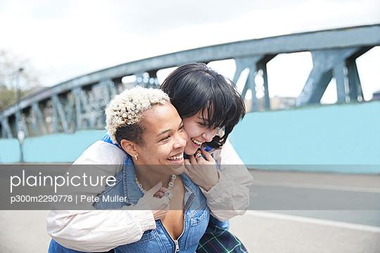 Happy woman enjoying piggyback ride from girlfriend - p300m2290778 by Pete Muller