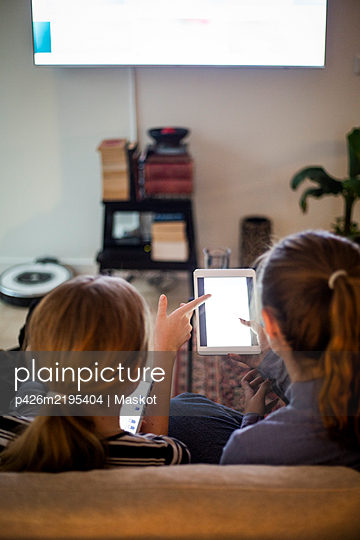 Rear view of sisters using portable information device while sitting in living room at home - p426m2195404 by Maskot