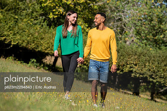 Smiling young couple walking in public park - p623m2294843 by Eric Audras