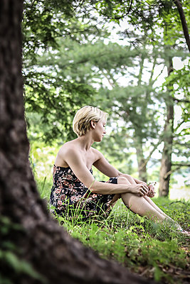Sad woman with blond hair sitting in the forest - p1019m1425481 by Stephen Carroll