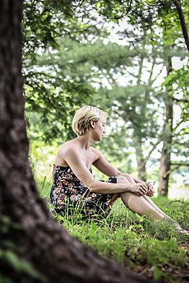 Blonde Frau sitzt traurig im Wald - p1019m1425481 von Stephen Carroll