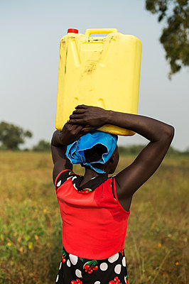 Africa, Uganda, Woman carrying water canister on her head - p1167m2283482 by Maria Schiffer