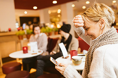 Young happy woman using smartphone in a cafe - p300m2058978 by Katharina Mikhrin