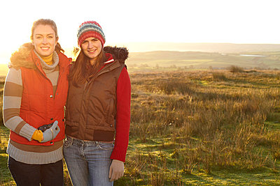 Women smiling together outdoors - p42918513f by Tim Hall