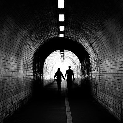 Couple walking into the light, York tunnel, York, England, United Kingdom - p871m2143256 by Karen Deakin
