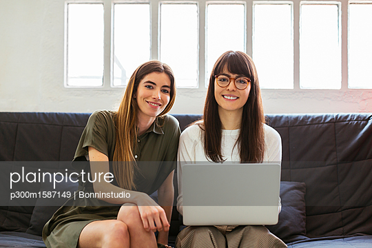 Two smiling young women sitting on couch in office with laptop - p300m1587149 von Bonninstudio