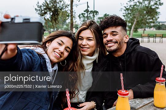 Smiling friends taking selfie through vintage camera at park - p300m2257532 by Xavier Lorenzo